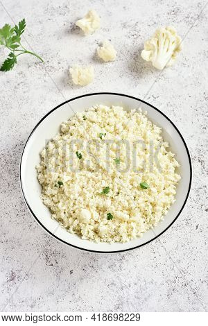 Cauliflower Rice In A Bowl On Light Stone Background. Close Up View