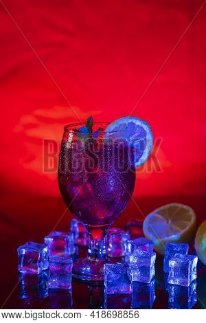 Refreshing Cocktail Drink Under A Mix Of Red And Blue Light In A Disco, Pub Or Bar. Concept Of Fun A