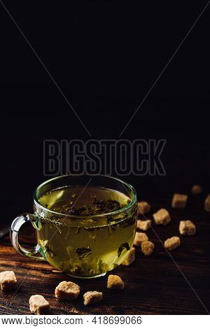 Cup Of Herbal Tea With Refined Sugar On A Wooden Background
