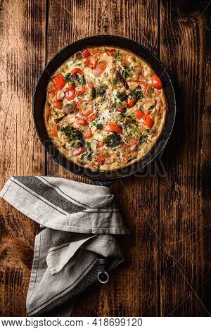 Vegetable Frittata With Broccoli, Red Bell Pepper And Herbs In Cast Iron Skillet. View From Above