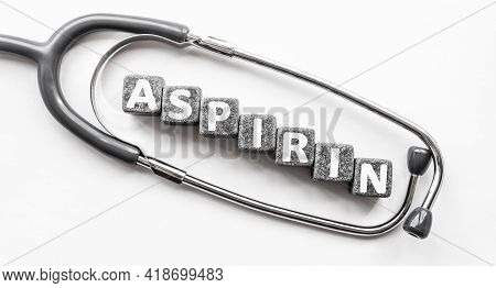 Stone Block Form Word Aspirin With Stethoscope. White Background. Medical Concept. Drug, Relieves Pa