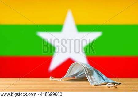 A Medical Mask Lies On The Table Against The Background Of The Flag Of Myanmar. The Concept Of A Man