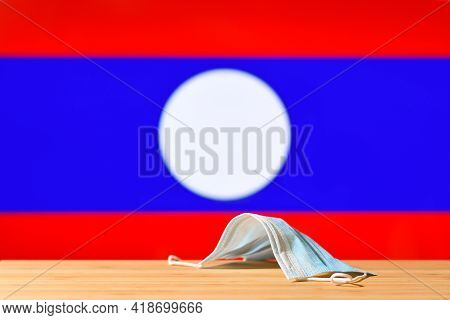 A Medical Mask Lies On The Table Against The Background Of The Flag Of Laos. The Concept Of A Mandat