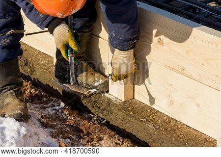 A Worker Hammers A Nail At A Construction Site. Installation Of Wooden Formwork. Construction Work
