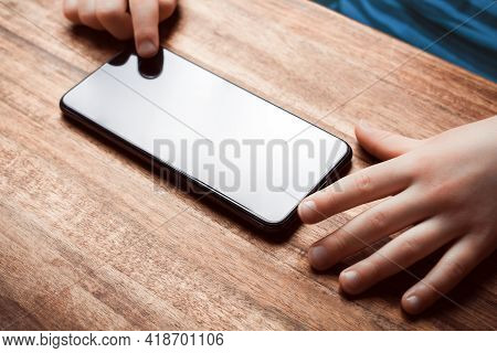 Child Playing With Smartphone On A Table - Prevent Child Smartphone Addiction Concept