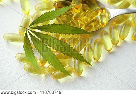 Cannabis Oil Capsule Concept, Cbd Oil Capsules And Hemp Leaves. Macro Close Up Of Capsules Of Biolog
