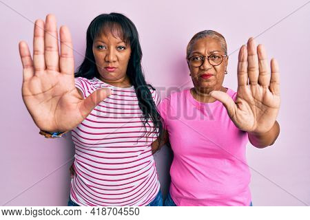 Hispanic family of mother and daughter hugging together with love with open hand doing stop sign with serious and confident expression, defense gesture