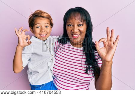 Hispanic family of mother and son hugging together with love doing ok sign with fingers, smiling friendly gesturing excellent symbol