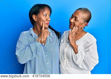 Hispanic family of mother and daughter hugging together with love serious face thinking about question with hand on chin, thoughtful about confusing idea