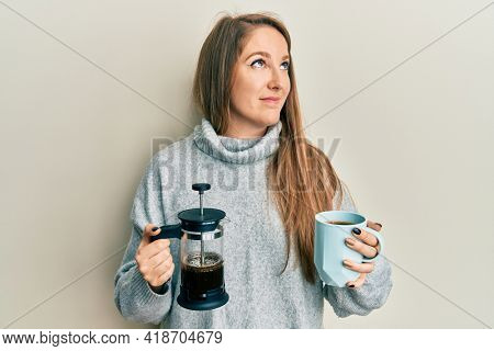 Young blonde woman drinking a cup of italian coffee smiling looking to the side and staring away thinking.