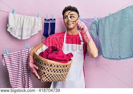 Handsome hispanic man doing laundry holding wicker basket looking for a stain smiling looking to the side and staring away thinking.