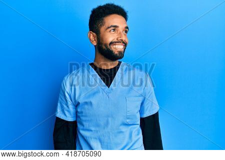 Handsome hispanic man with beard wearing blue male nurse uniform looking away to side with smile on face, natural expression. laughing confident.