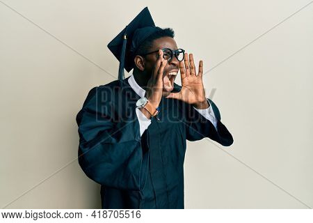 Handsome black man wearing graduation cap and ceremony robe shouting angry out loud with hands over mouth