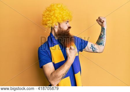 Redhead man with long beard football hooligan cheering game wearing funny wig showing arms muscles smiling proud. fitness concept.