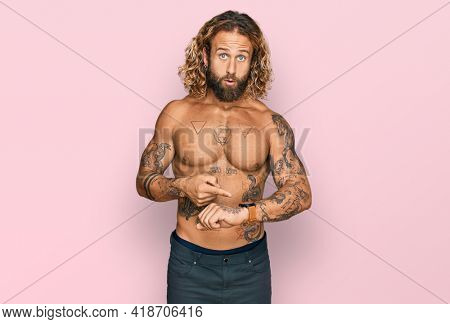 Handsome man with beard and long hair standing shirtless showing tattoos in hurry pointing to watch time, impatience, upset and angry for deadline delay