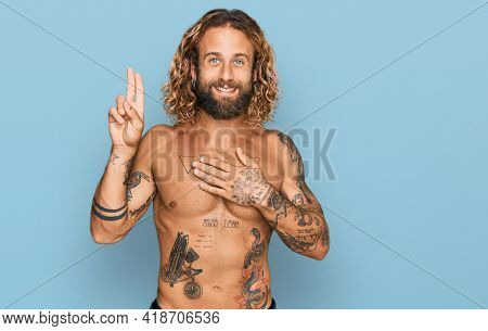 Handsome man with beard and long hair standing shirtless showing tattoos smiling swearing with hand on chest and fingers up, making a loyalty promise oath