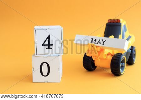 Calendar For May 4: A Toy Yellow Tractor With Numbers On Cubes 0 And 4, The Name Of The Month In Eng