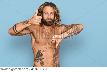 Handsome man with beard and long hair standing shirtless showing tattoos doing thumbs up and down, disagreement and agreement expression. crazy conflict
