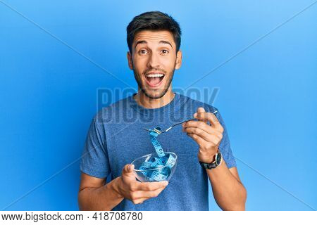 Young handsome man eating measure meter doing diet for weight loss celebrating crazy and amazed for success with open eyes screaming excited.