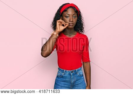 Beautiful african young woman wearing casual clothes mouth and lips shut as zip with fingers. secret and silent, taboo talking