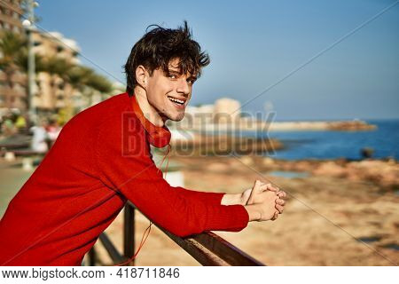 Young hispanic man using headphones leaning on the balustrade at the beach