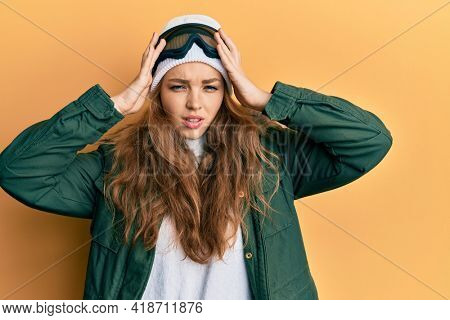 Beautiful blonde caucasian woman wearing snow wear and sky glasses suffering from headache desperate and stressed because pain and migraine. hands on head.