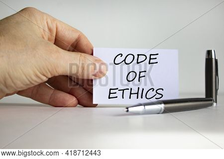 Code Of Ethics Symbol. White Paper With Words 'code Of Ethics' In Businessman Hand, Metalic Pen. Bea