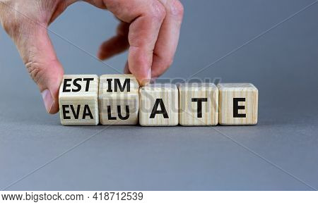 Estimate Or Evaluate Symbol. Businessman Turns Wooden Cubes And Changes The Word 'evaluate' To 'esti