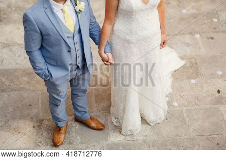 The Bride And The Groom Stand Side By Side And Hold Each Others Hands, The Groom Holds His Hand In H