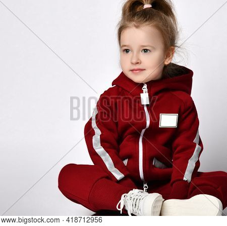 Cute Little Preschooler Girl, Dressed In A Warm Tracksuit With A Hood And White Sneakers, Sits On On