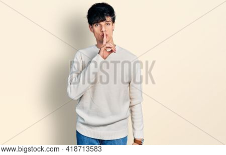 Handsome hipster young man wearing casual winter sweater asking to be quiet with finger on lips. silence and secret concept.