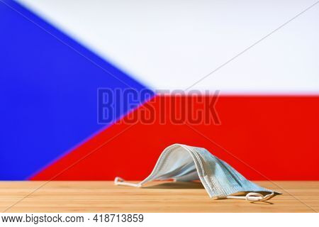 A Medical Mask Lies On The Table Against The Background Of The Flag Of Czech Republic. The Concept O