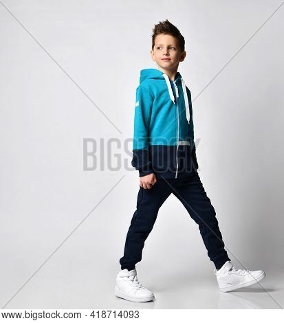 Teen Boy Posing Together In Modern Stylish Tracksuit With Hood, Pants And Sneakers, On White Backgro