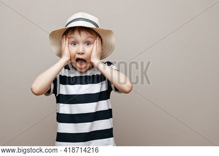 Portrait Of A Surprised Cute Boy Standing Isolated On A Gray Background. Hands Near The Open Mouth,