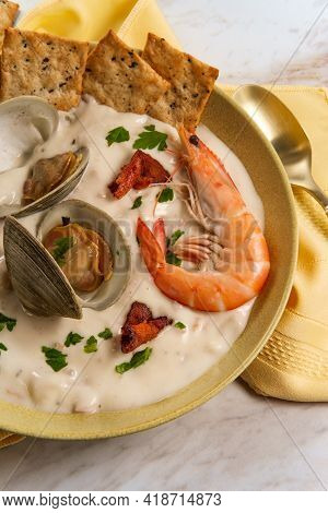 Fresh Hot New England Clam Chowder Soup With Whole Shrimp Crackers And Parsley Garnish