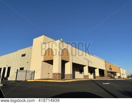 Columbia County, Ga Usa - 01 21 21:  Empty Retail Building With Security Gate Clear Blue Sky - Colum
