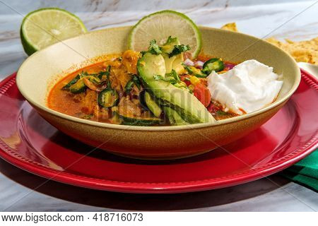 Hearty And Spicy Chicken Tortilla Soup With Hot Peppers And Avocado Garnish