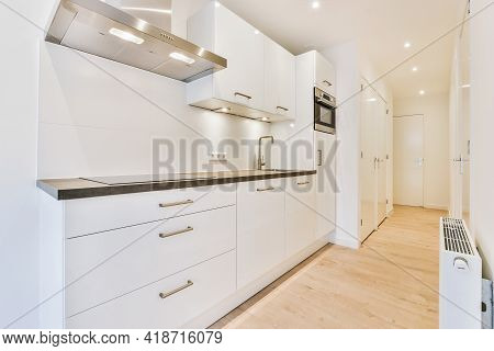 Interior Of Spacious Kitchen With White Cupboards And Shiny Appliances In New Apartment