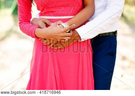 The Bride In A Long Bright Pink Dress And The Groom Stand Hugging Tenderly, The Bride Put Her Hands