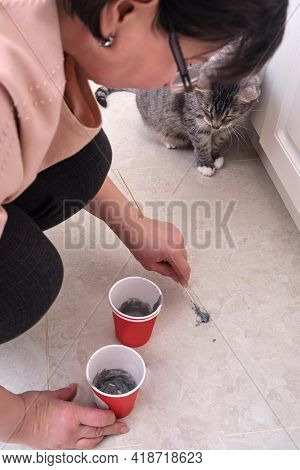 A Senior Woman Fills A Hole In The Floor With Cement. Cementing To Repair Damaged Tiles