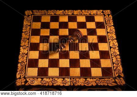 The Black Chess King Lies On The Chessboard After Losing The Game. White Won At Chess