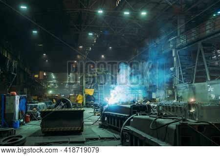 Metal Welder Working With Arc Welding Machine At Metallurgical Foundry Factory Workshop Interior. Me
