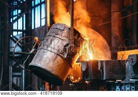 Metal Casting Process In Foundry, Liquid Metal Pouring From Container To Mold With Clubs Of Steam An