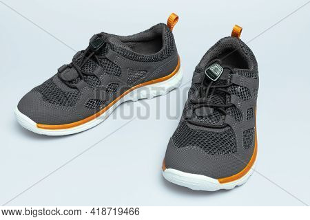 Children Grey Sneakers With Rubber Sole On Blue Background, Closeup.