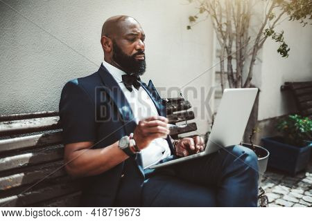 A Fancy Handsome Bald Bearded African Senior With Glasses In A Hand Is Working On A Netbook Outdoors