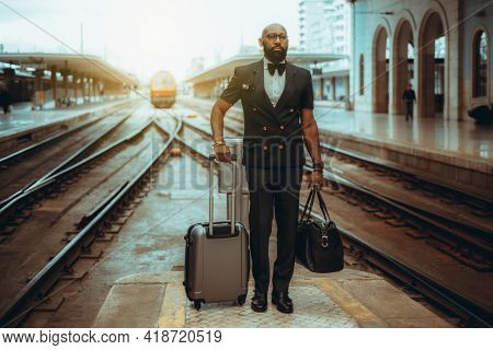 A Serious Bearded Hairless Well-dressed Black Man Entrepreneur In A Suit With A Bow-tie And Luggage
