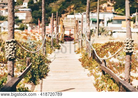 A Narrow Passage Leading Inland From The Beach With A Boardwalk And Posts Connected With Ropes, Shal