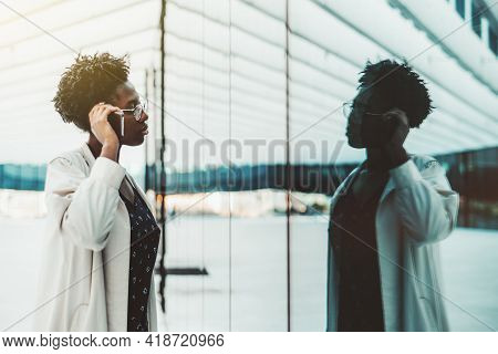 A Portrait Of A Young Fancy African Business Lady In A White Trench Standing In Front Of A Glass Mir