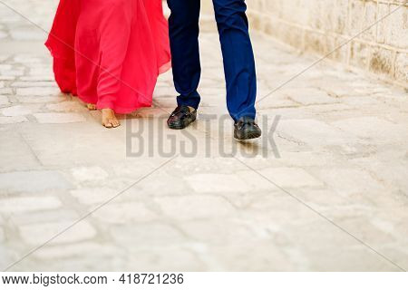 Barefoot Bride In A Long Bright Pink Dress And The Groom Walking Along A Cobbled Road, Close-up
