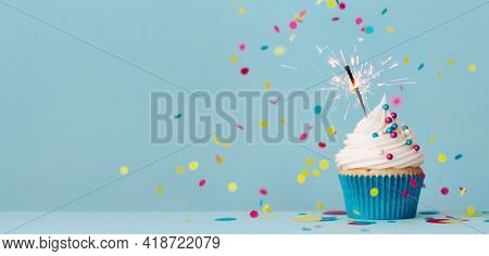 Birthday party background with birthday cupcake, celebration sparkler and colorful falling confetti